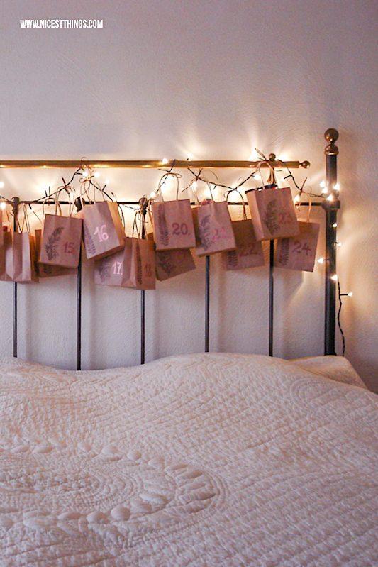 Adventskalender mit Lichterkette am Bett aus bestempelten Papiertüten #adventskalender #lichterkette #advent #weihnachten #papiertüten
