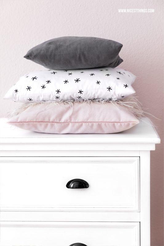 Kissenstapel gestapelte Kissen auf weißer Kommode vor rosa Wand