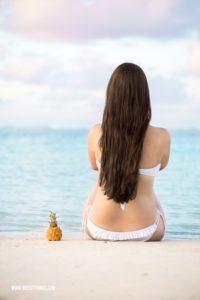 Frau am Strand mit Baby Ananas