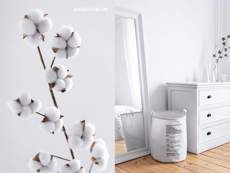 Baumwollzweig auf weißer Kommode und Wäschesack