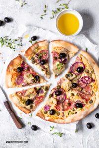 Pizza Bianca Rezept mit Kichererbsen Creme, Salami, Kapern, Artischocken und Oliven #pizza #pizzarezepte #pizzabianca #artischocken #kichererbsen #oliven #salami #sardellen #kapern #italianfood