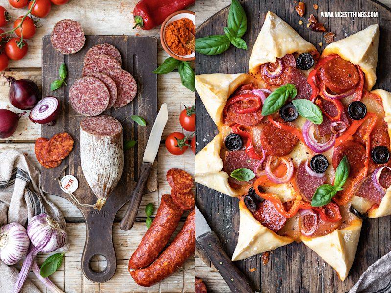 Pizza Stern von oben sternförmige Pizza Party Pizza Rezept Pizzarezept mit ungarischer PICK Salami und Kolbasz auf Brett, Paprika, Oliven und Mozzarella